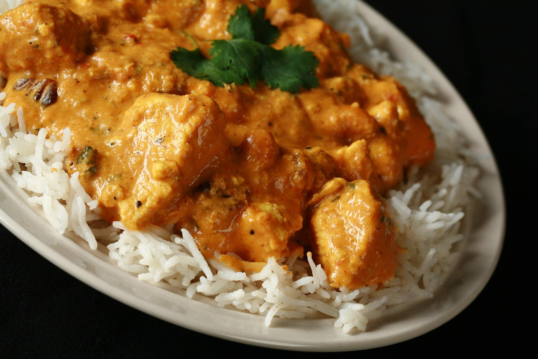 A plate with rice smothered in a creamy Chicken Shahi Korma.