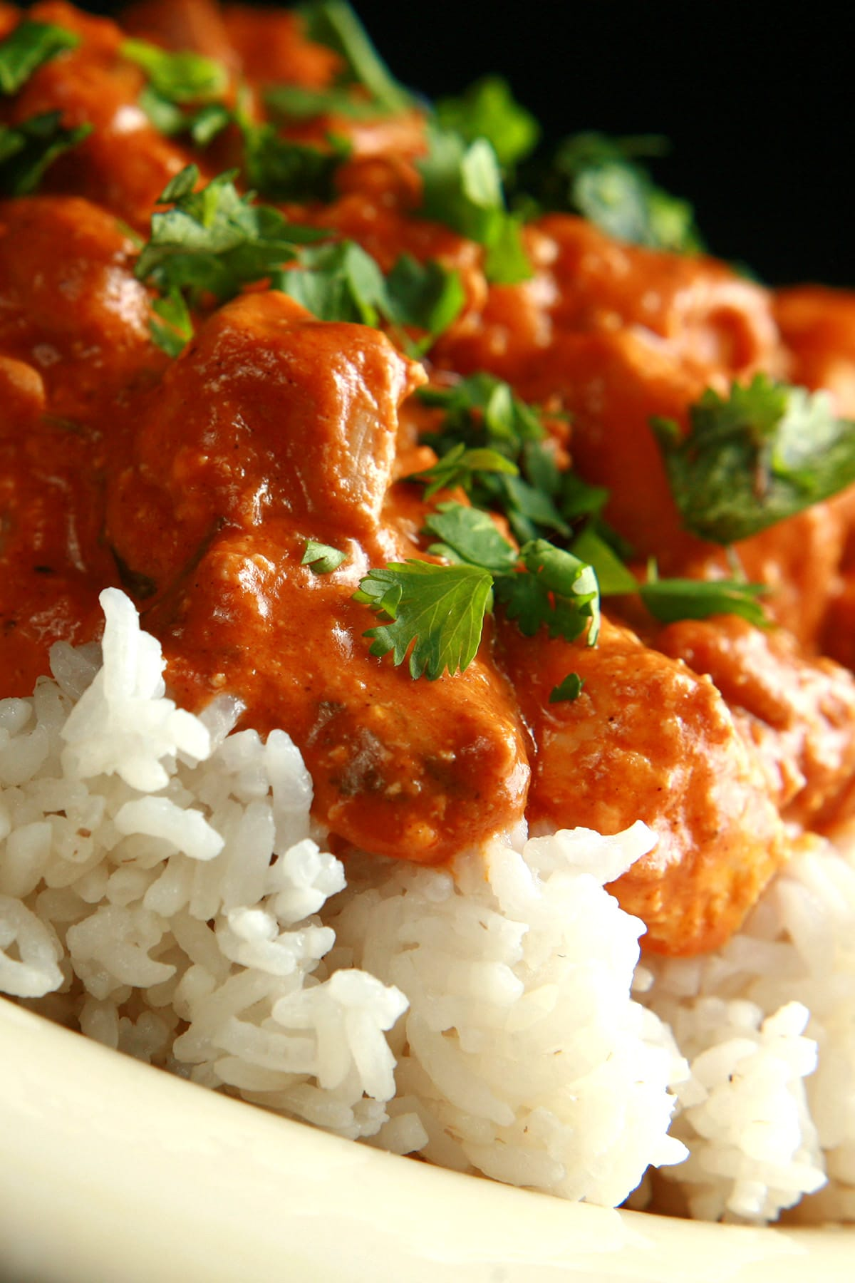 A close up view of Butter Chicken - Chicken in a  creamy tomato sauce, served over rice.