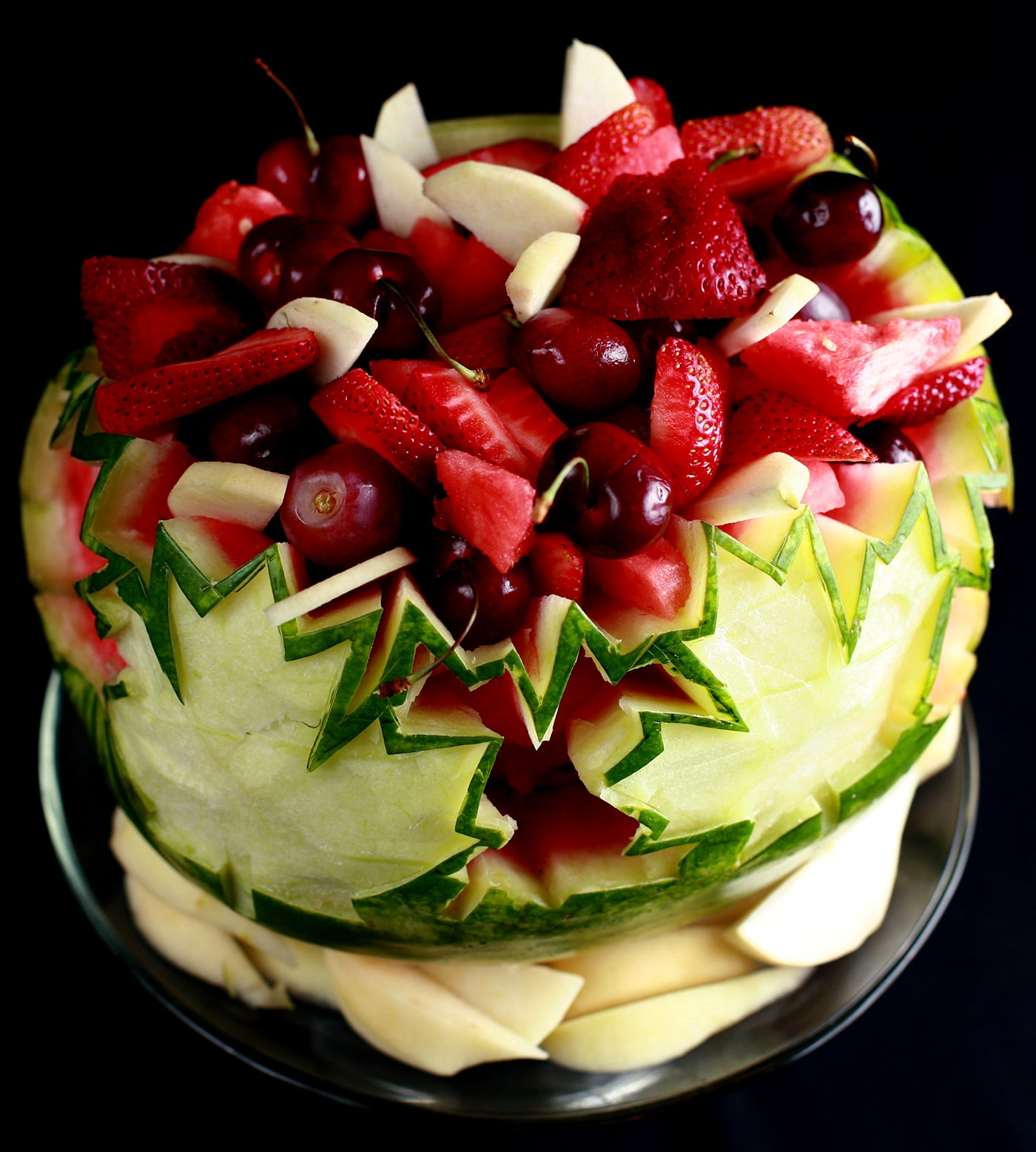 A Canada Day, Canadian Themed Watermelon Bowl. White and red maple leaves are carved into the watermelon, which is filled with red and white fruit.