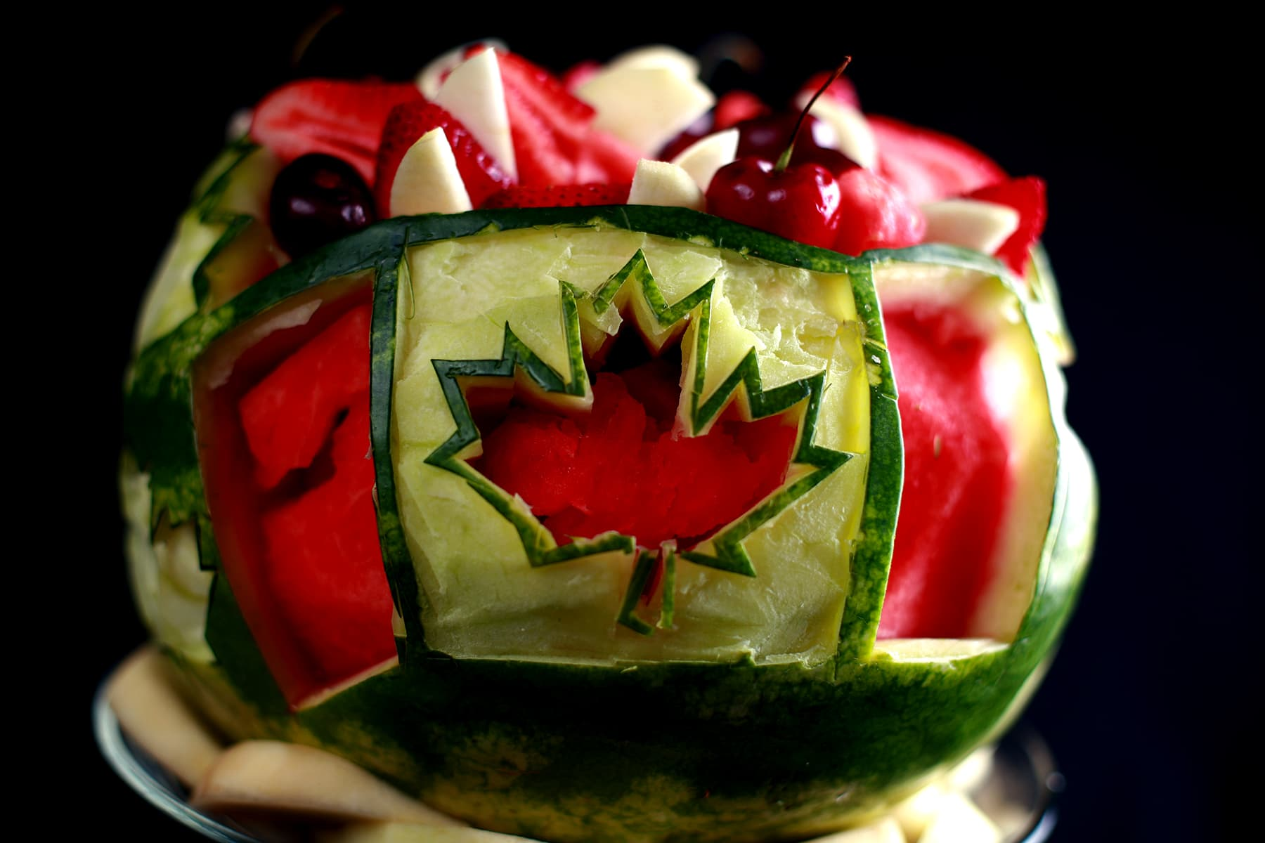 A Canada Day, Canadian Themed Watermelon Bowl. A Canadian flag is carved into the watermelon, which is filled with red and white fruit.