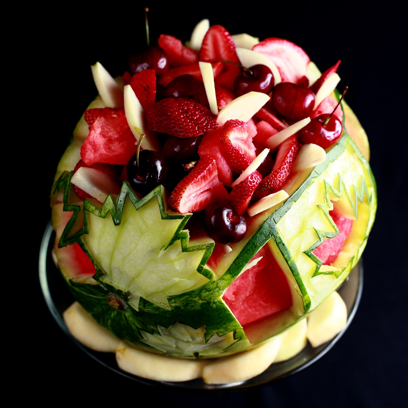 A Canada Day, Canadian Themed Watermelon Bowl. White and red maple leaves and a Canadian flag are carved into the watermelon, which is filled with red and white fruit.