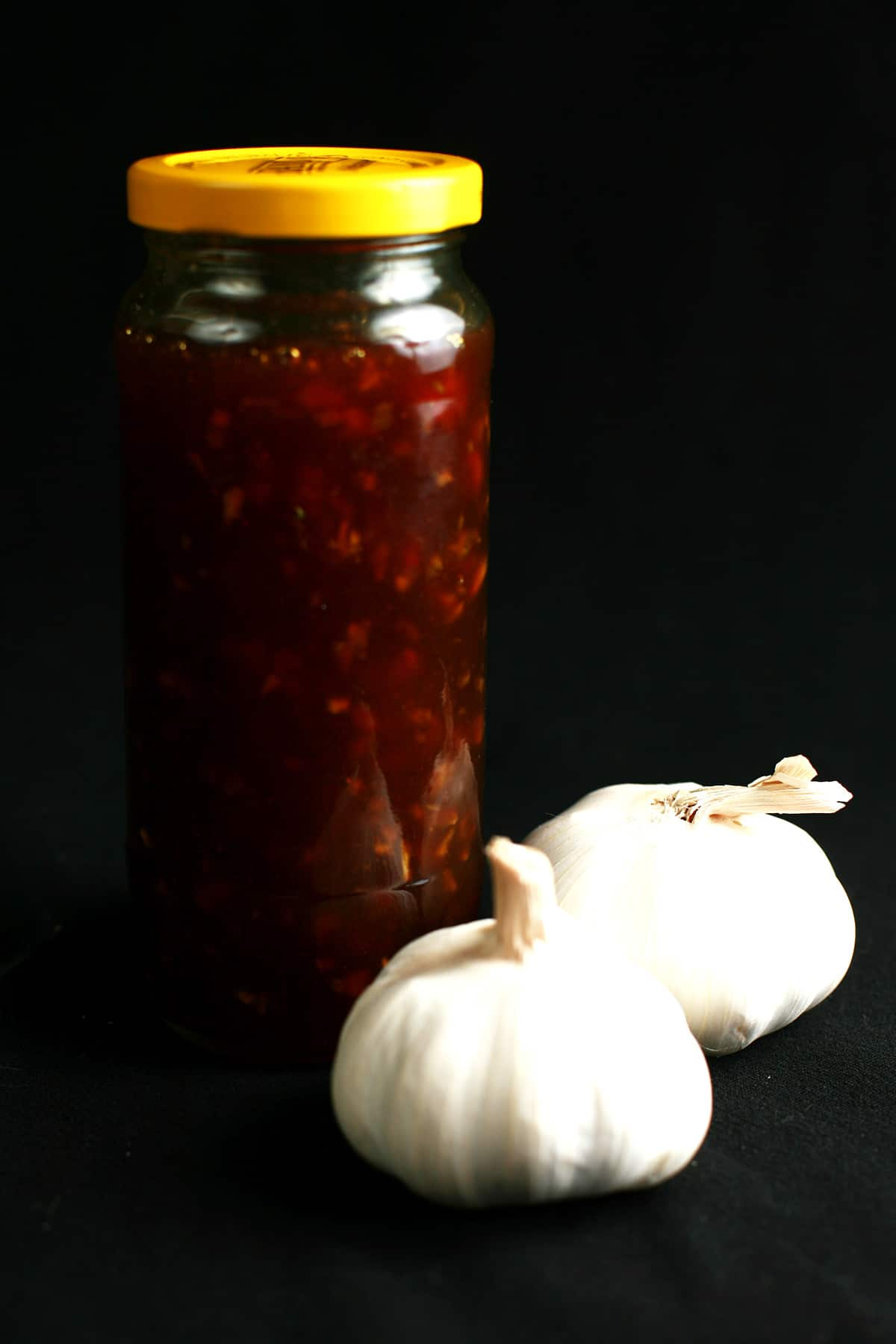 A tall, slender glass jar filled with homemade honey garlic sauce, a replica of the VH sauce. 2 whole bulbs of garlic rest at the base of the jar.