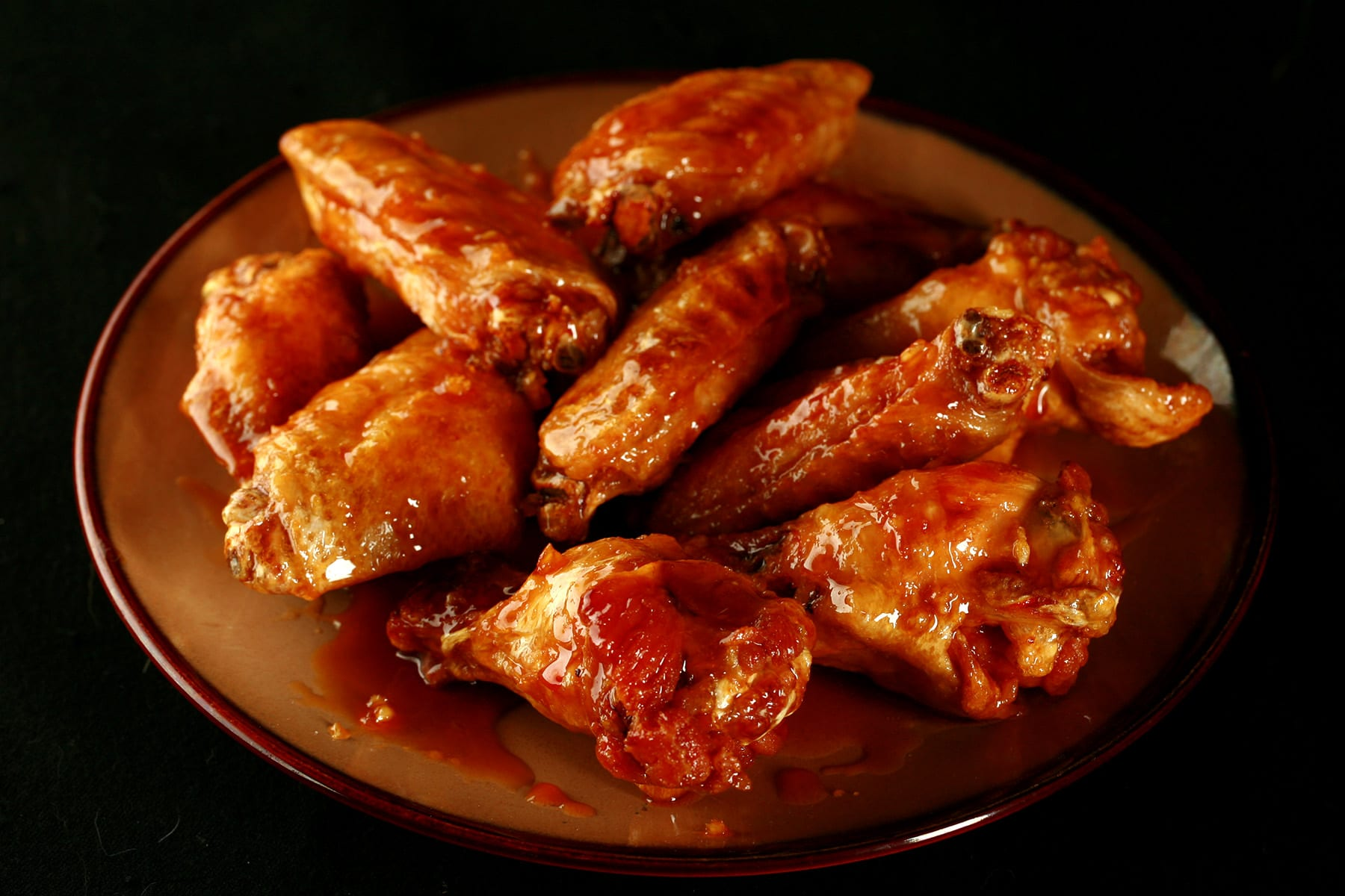 A close up view of a pile of honey garlic wings on a small brown plate.