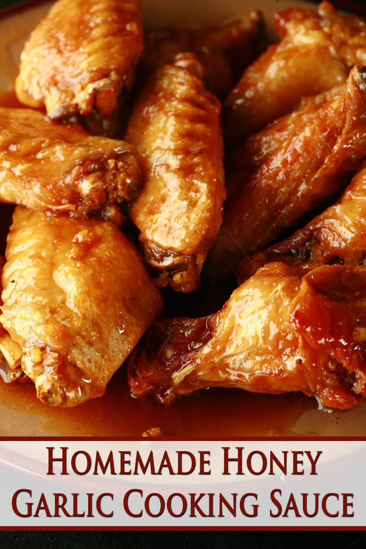 A close up view of a pile of honey garlic glazed wings on a small brown plate.