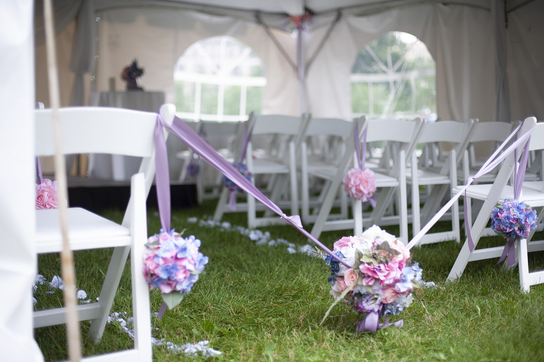 A white wedding tend with a pastel coloured silk flower pomander acting as an aisle block.