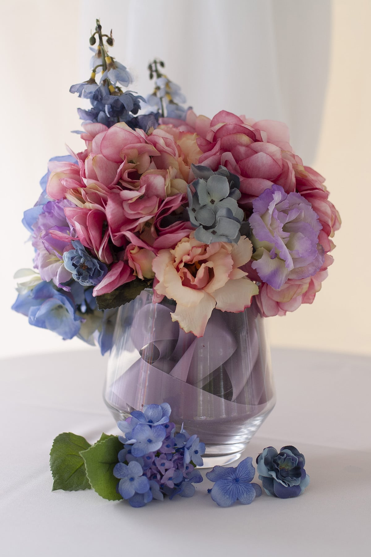 A vase with pastel silk hydrangeas and roses.