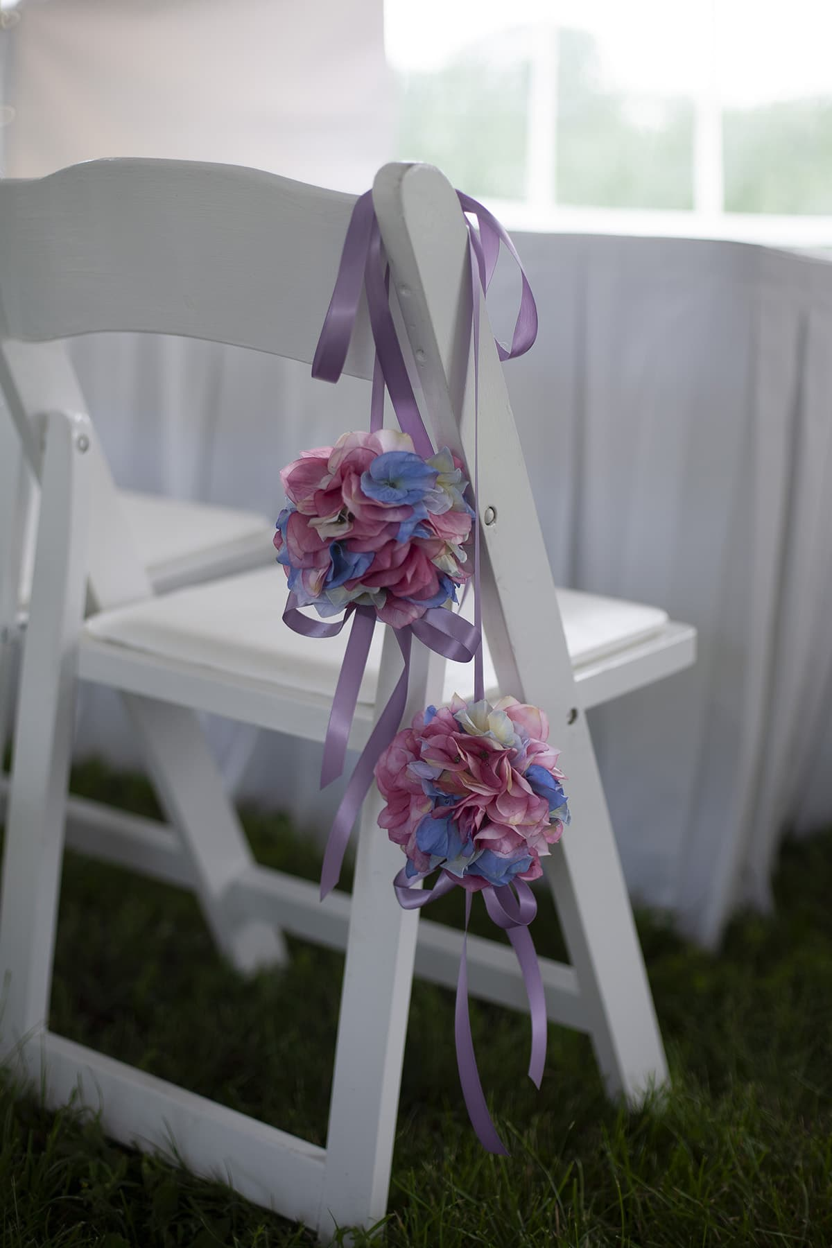 Pastel coloured pomanders draped over a white fold out ceremony chair.