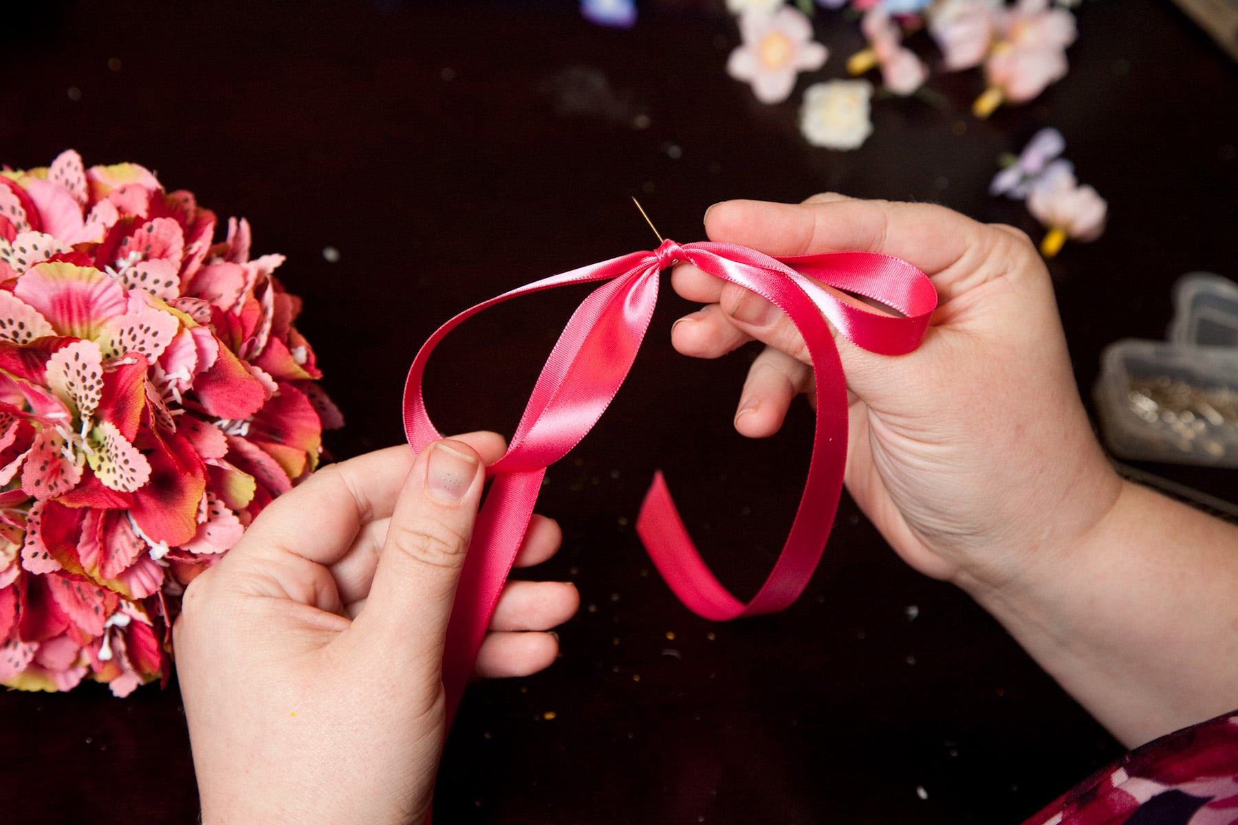 Two hands hold a pink ribbon. There is a pin inserted in the middle of it.
