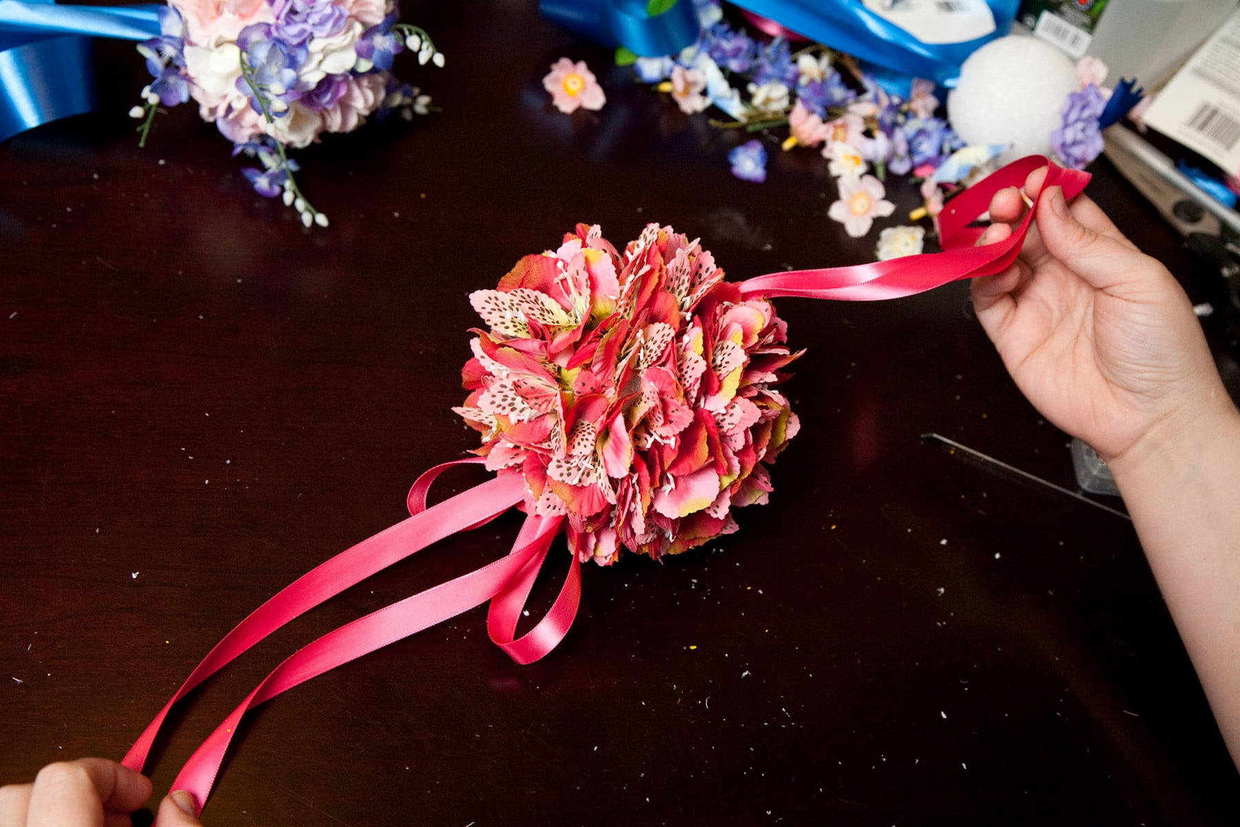 Two hands hold a pomander made of pink silk flowers and hot pink ribbon.