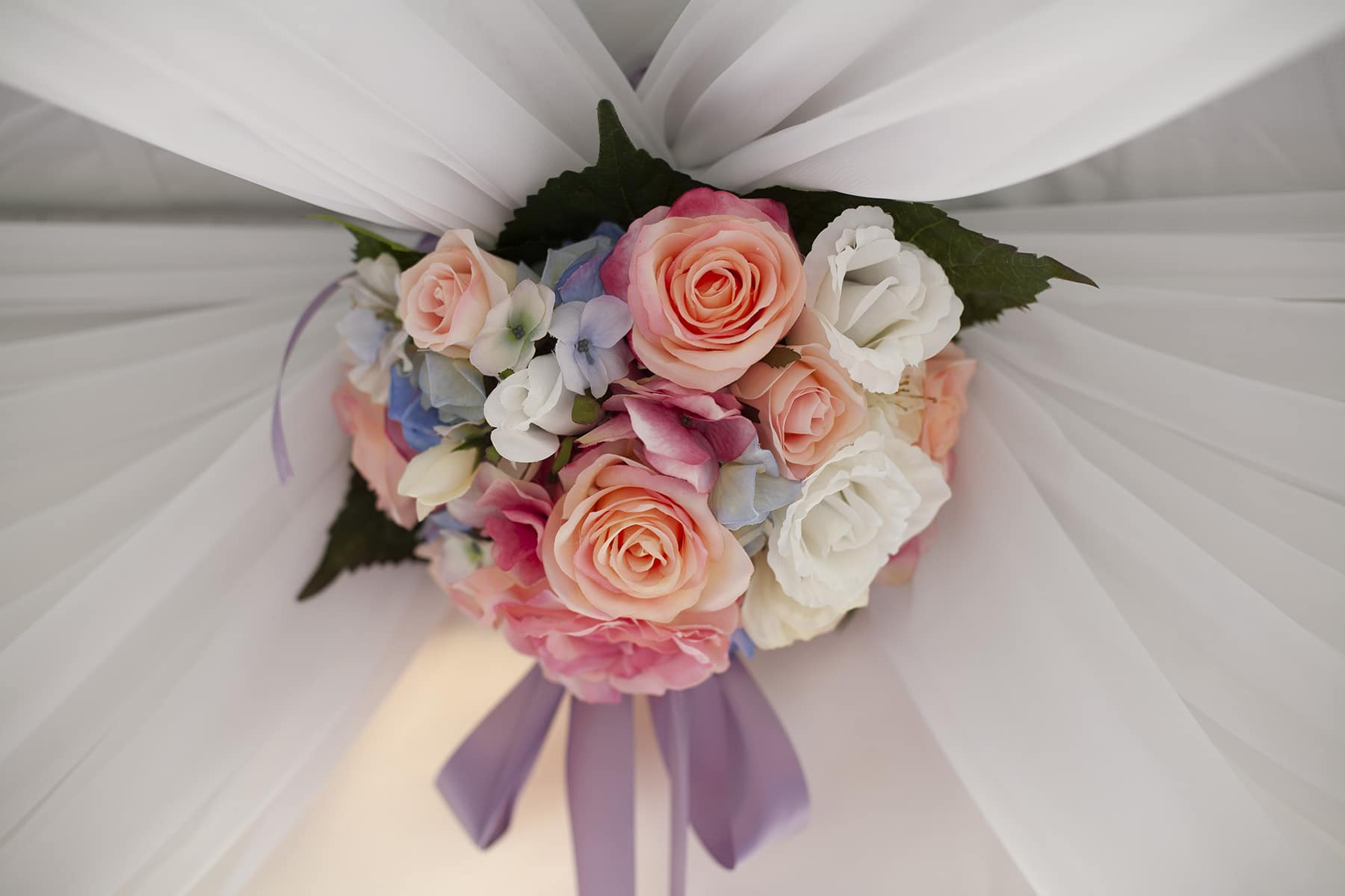 A large dome arrangement made of pastel roses and filler flowers.