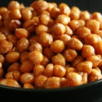 A shallow white and black bowl, piled high with roasted chickpeas.