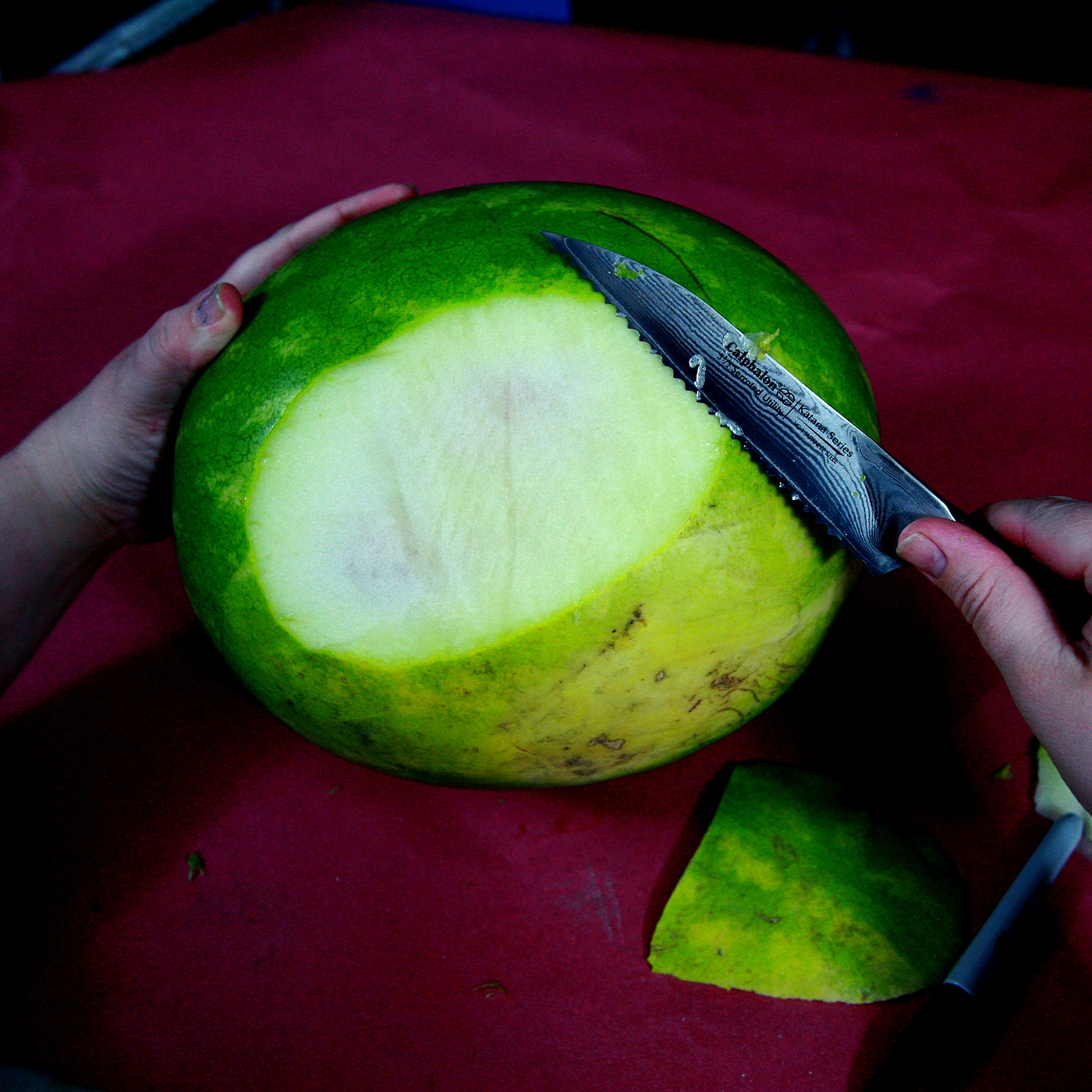 A large round of rind is being cut off the bottom of a watermelon.