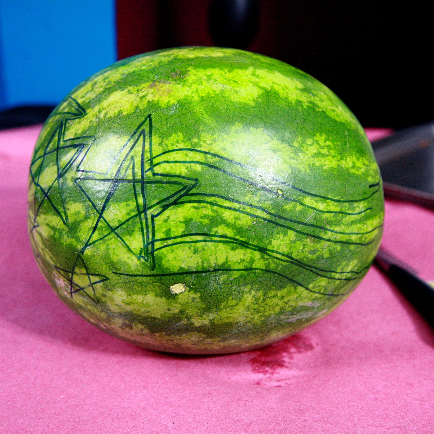 A stars and stripes design has been drawn on a watermelon with a black sharpie marker.