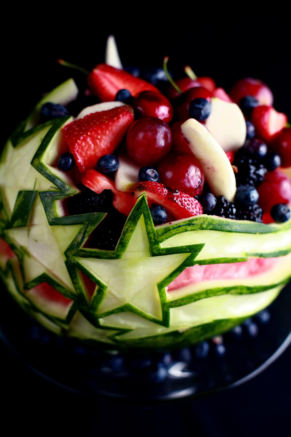An Independence Day Watermelon Bowl. It is carved with a stars and stripes design, and filled with red, white, and blue fruit.