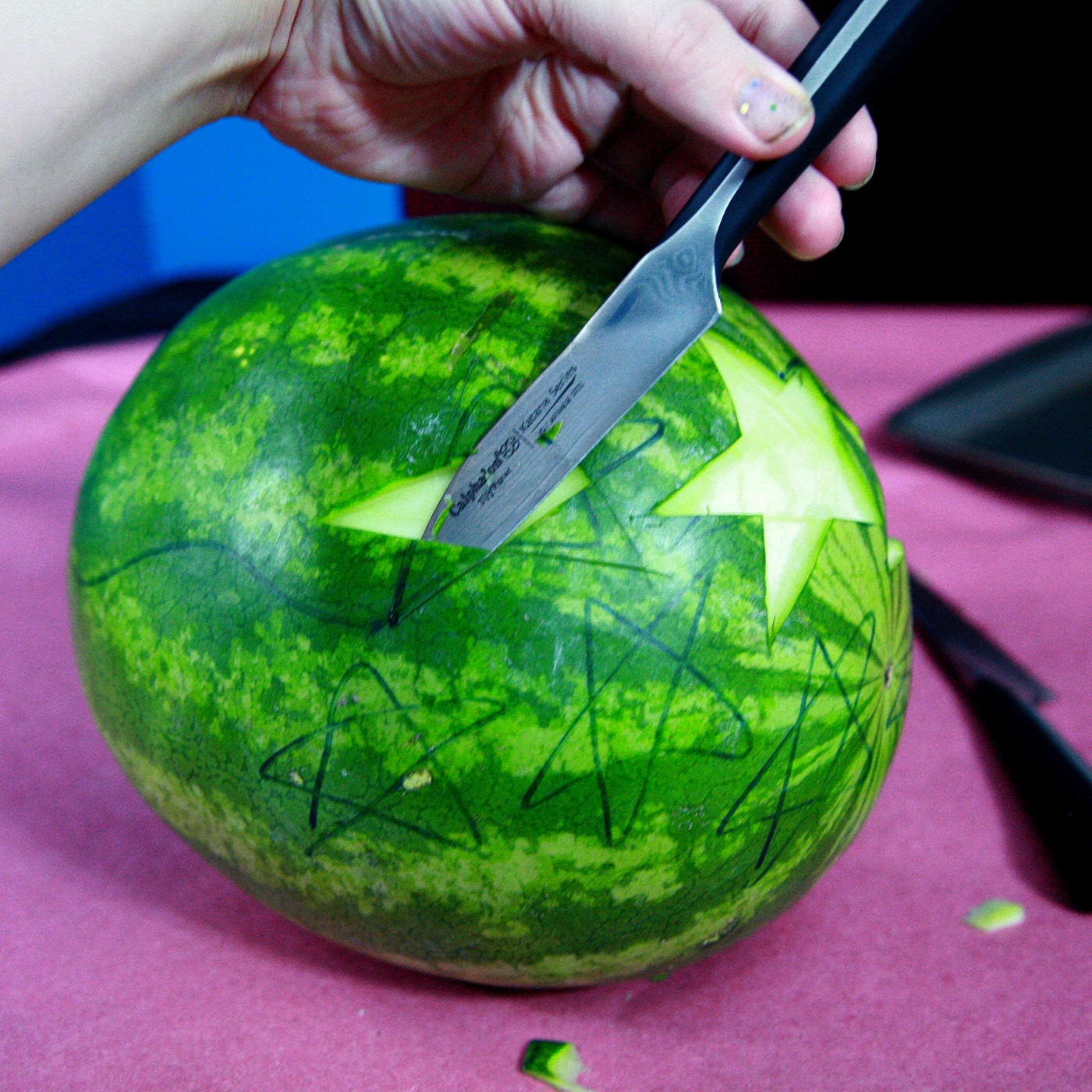 A hand holds a paring knife up to a cut made in a watermelon.