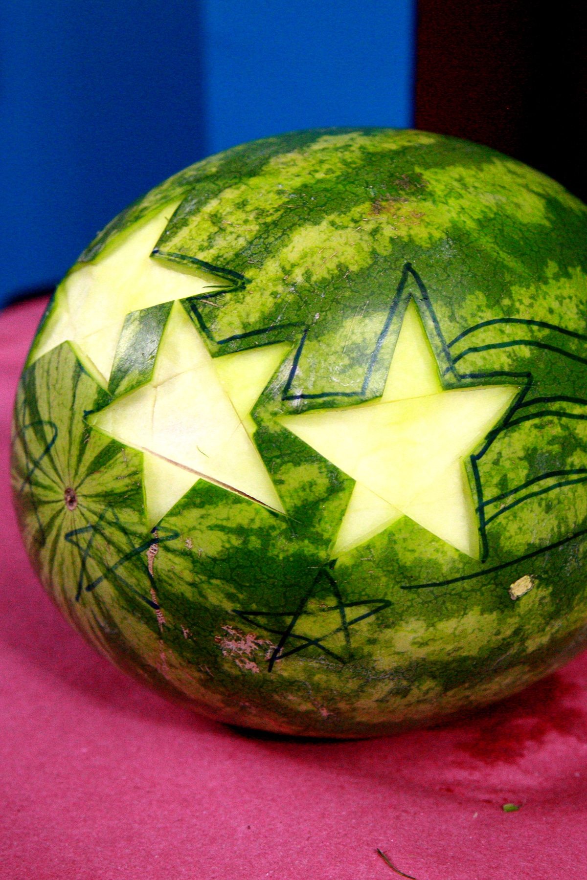 3 star shapes have been cut and carved out of a watermelon rind.