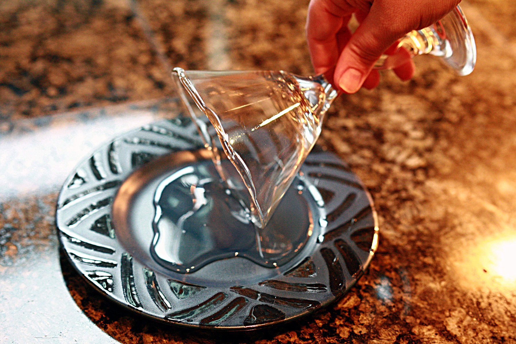 A hand dips the edge of a martini glass in a puddle of clear liquid, on a blue plate.