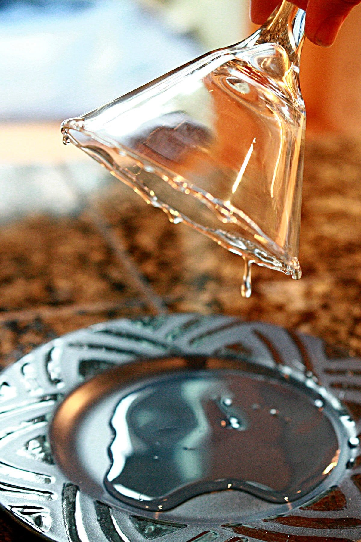 A hand holds a martini glass upside down over a blue plate, allowing excess corn syrup to drip off.