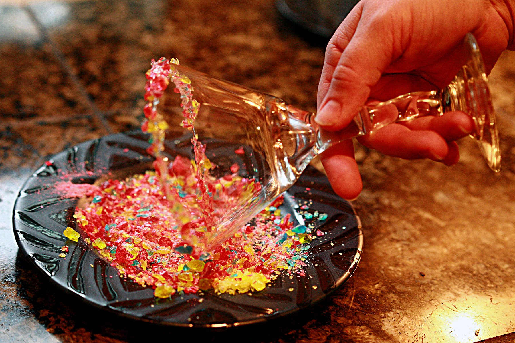 A hand twirls the rim of a martini glass in a dish of smashed up candy.