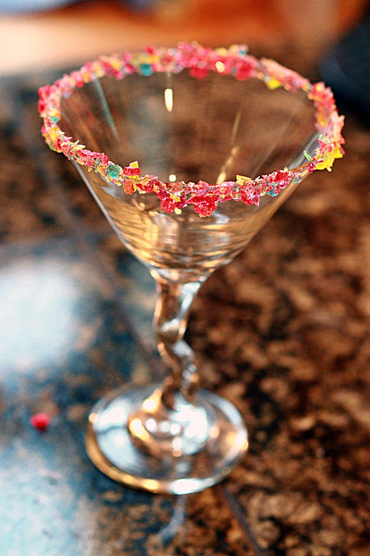 A martini glass stands on a granite countertop. Its rim is encrusted with tiny shards of multicoloured candy.