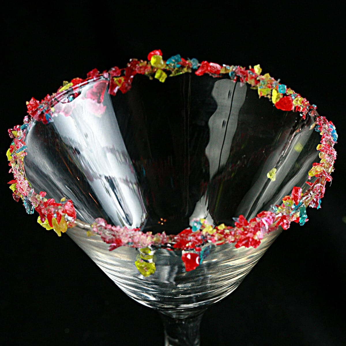 A martini glass with a candied cocktail rim, against a black background.