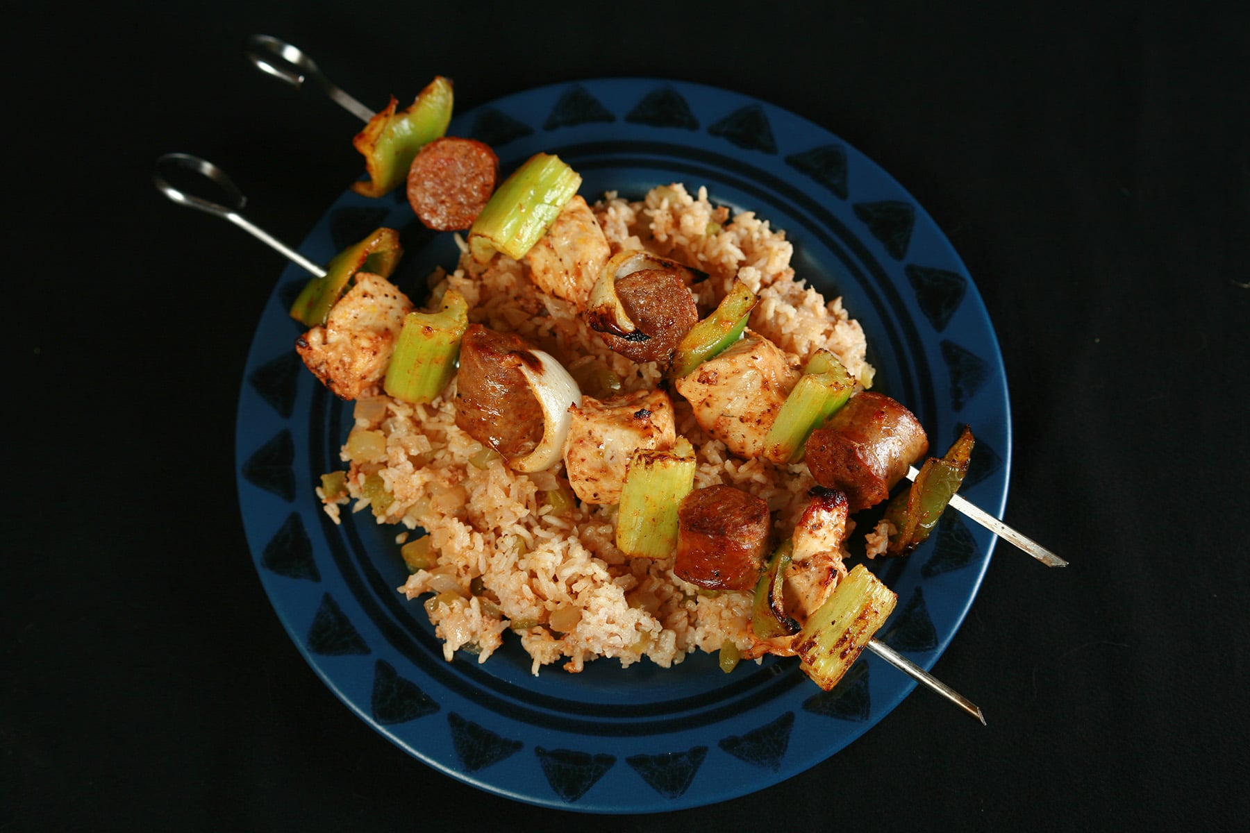 """Two grilled skewers of chicken, sausage, green onions, onion, and celery on a bed of intensely seasoned """"dirty"""" rice. rice."""