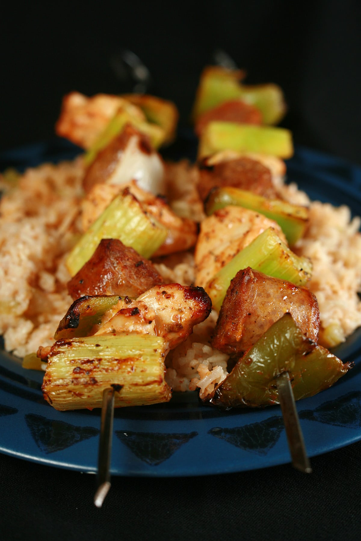 """Two grilled jambayala skewers of chicken, sausage, green onions, onion, and celery on a bed of intensely seasoned """"dirty"""" rice."""