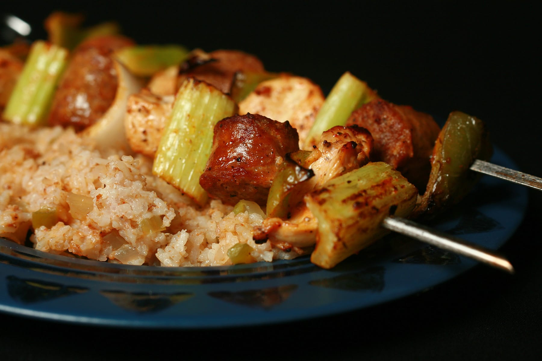 """Two grilled skewers of chicken, sausage, green onions, onion, and celery on a bed of intensely seasoned """"dirty"""" rice."""