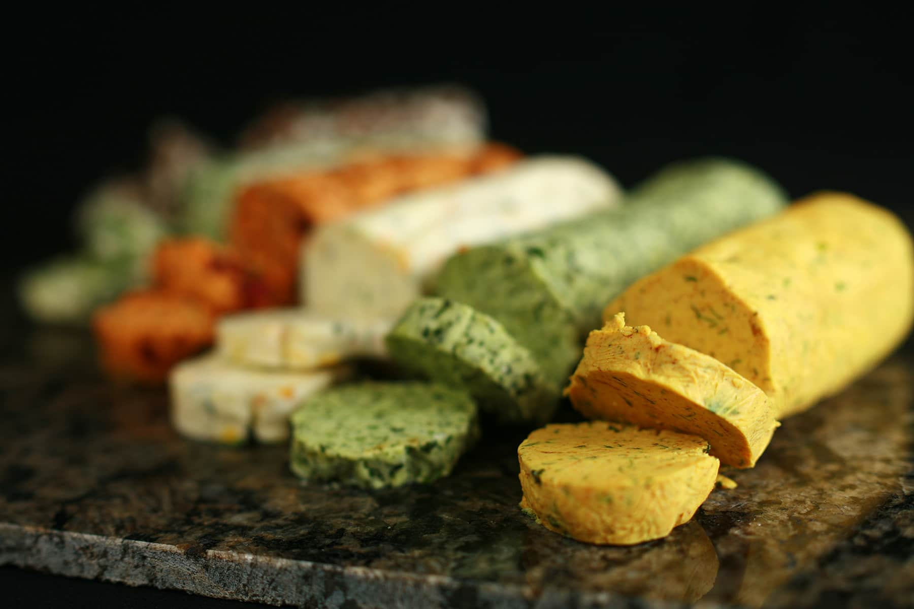 A row of compound butter logs in various colours and flavours.