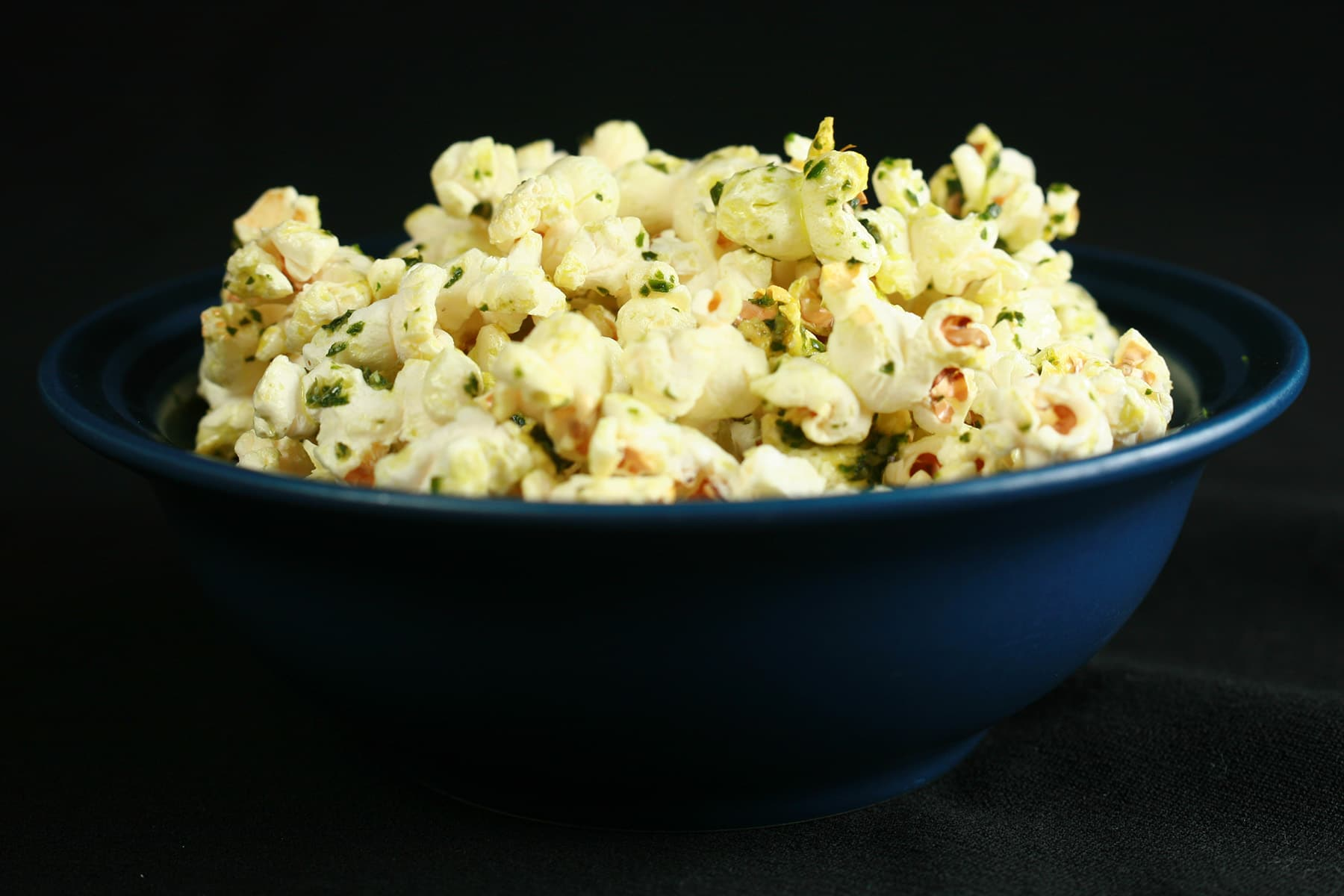 A bowl of popcorn with pesto butter.