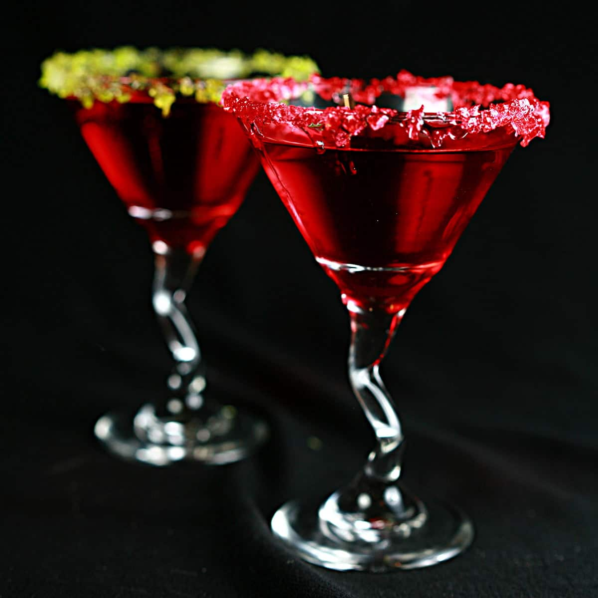 Two Jolly Rancher Martinis - a Red drink in a martini  glass.  One is rimmed with crushed green candy, the other is rimmed with a red crushed candy.