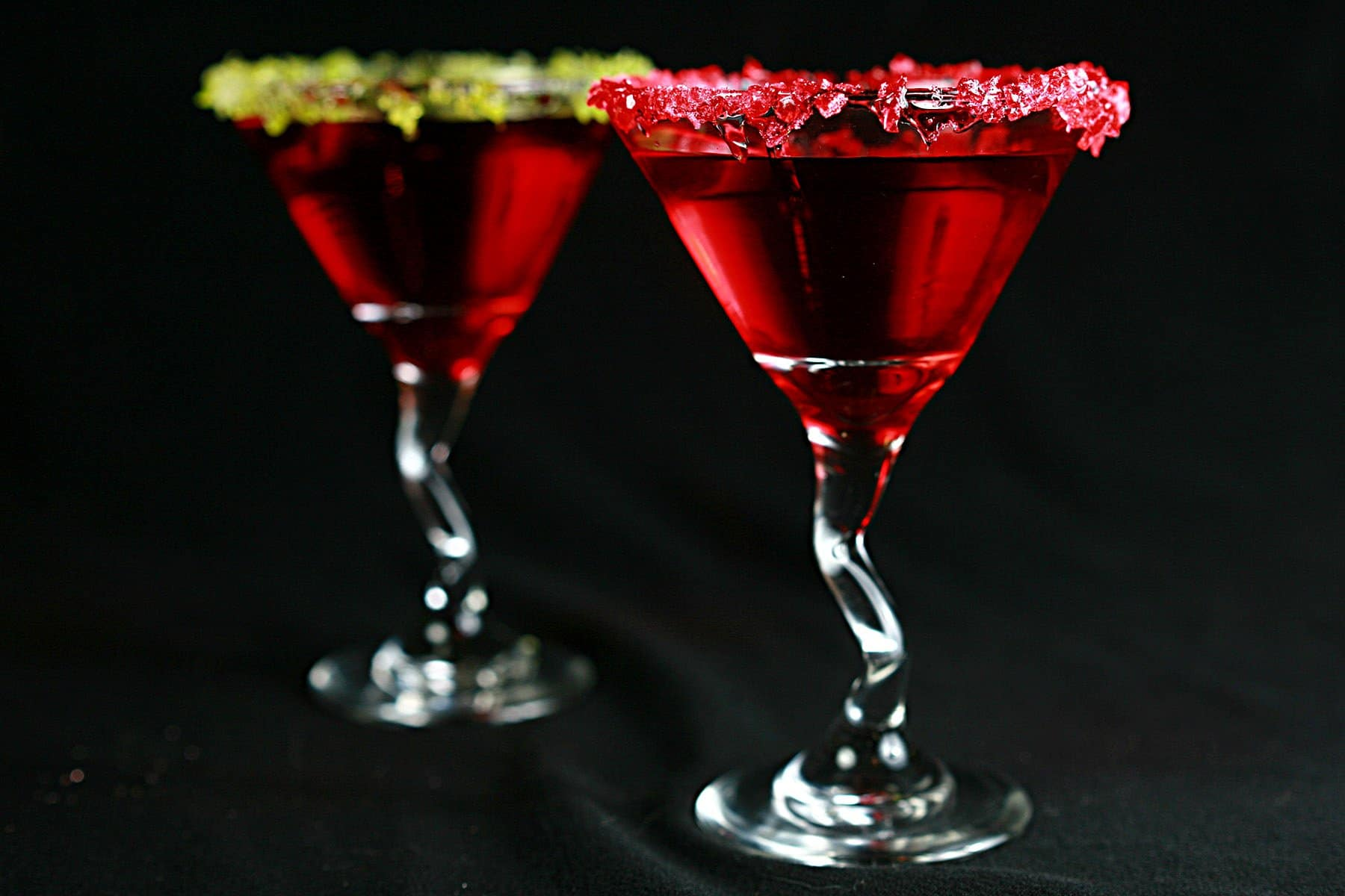 Two Martini cocktails - a Red drink in a martini glass. One is rimmed with crushed green candy, the other is rimmed with a red crushed candy.