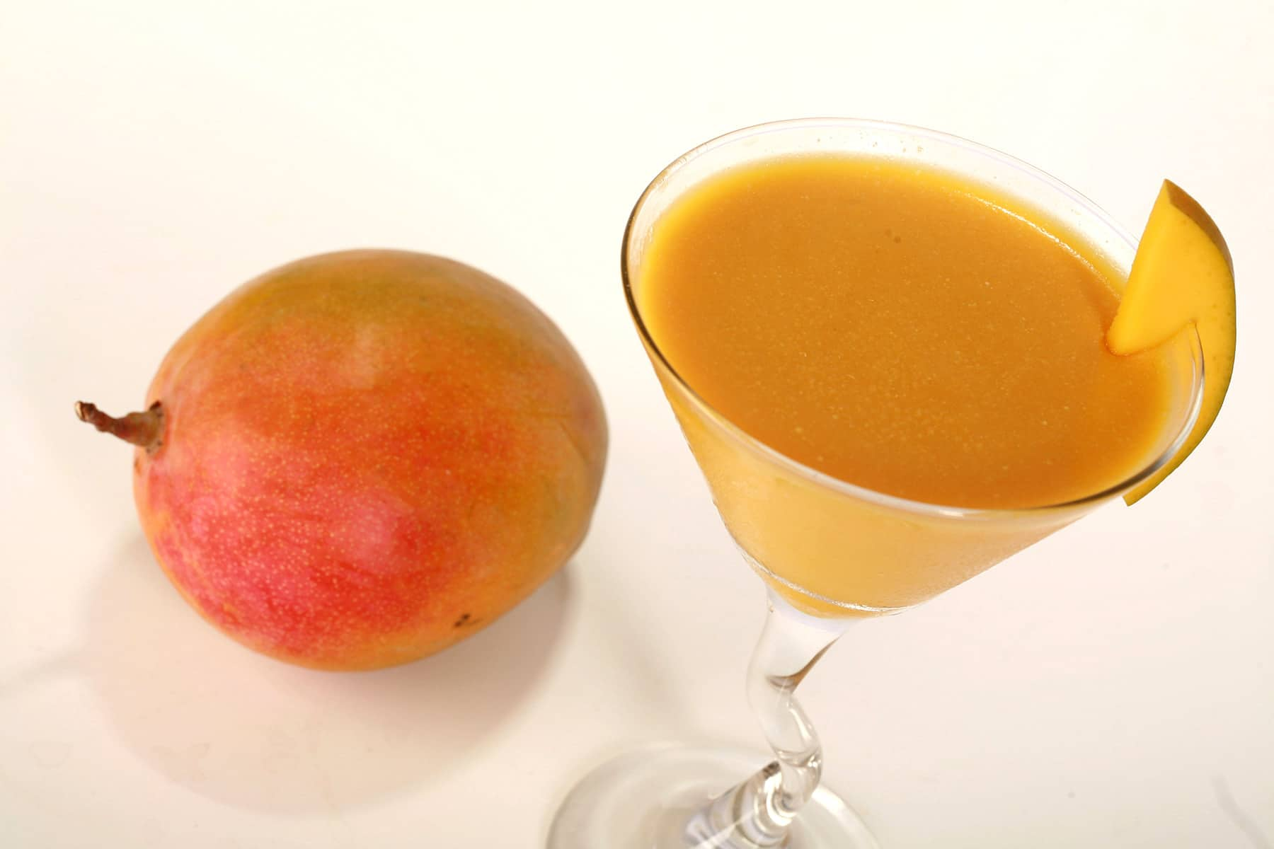 A martini glass of mango daiquiri panna cotta, with a whole mango next to it.