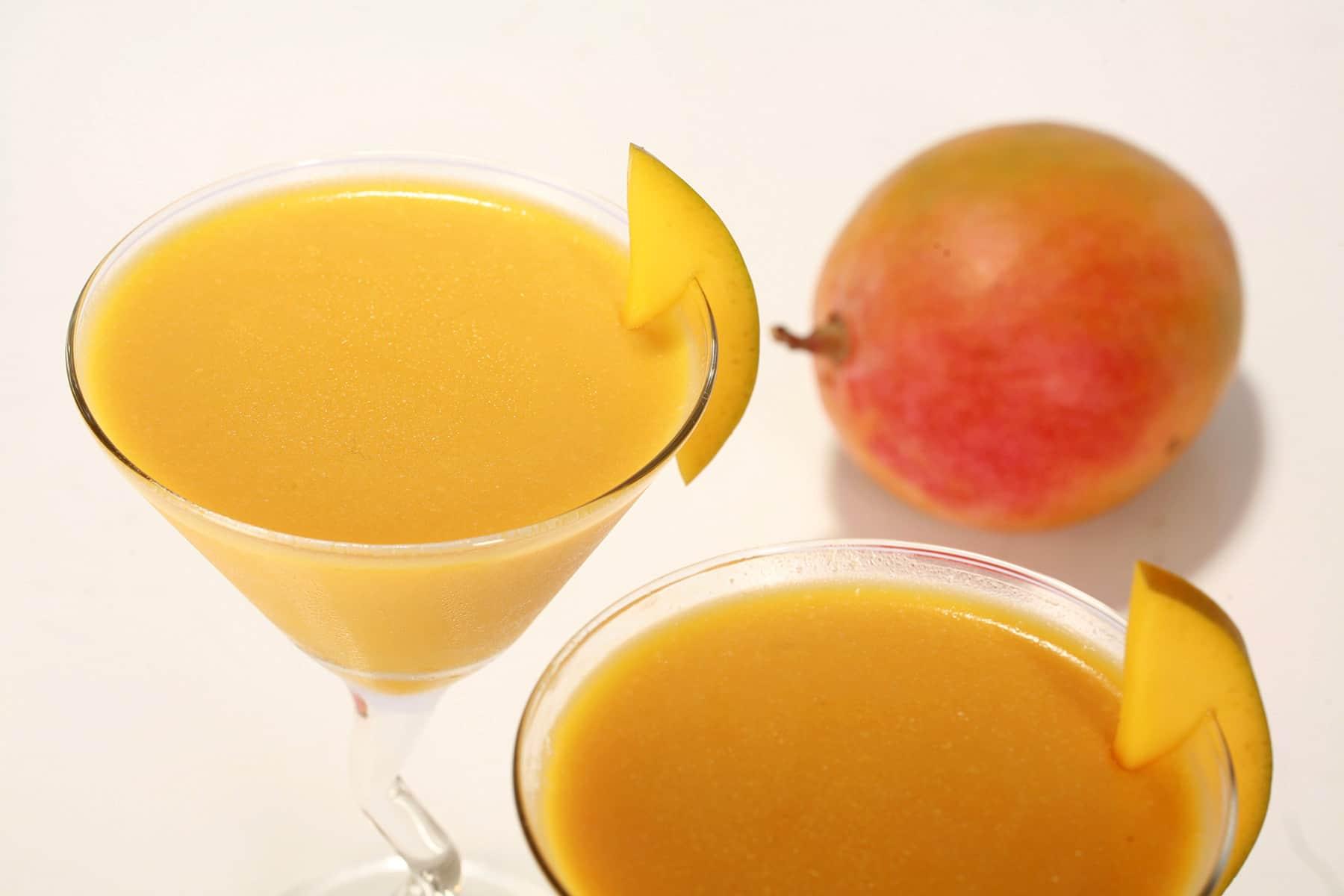 2 Mango daiquiri panna cottas, with a whole fresh mango beside them.
