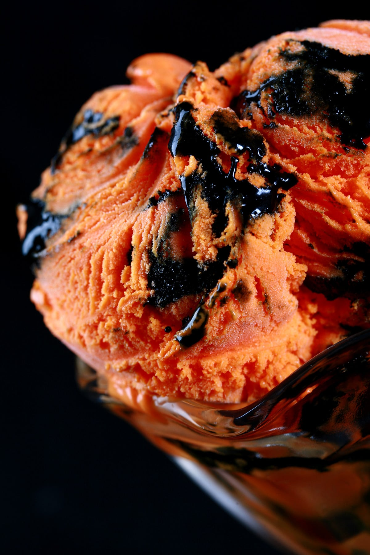 A fluted glass dessert bowl with 2 big scoops of Tiger Tail Ice Cream - Orange ice cream with a licorice ribbon throughout.