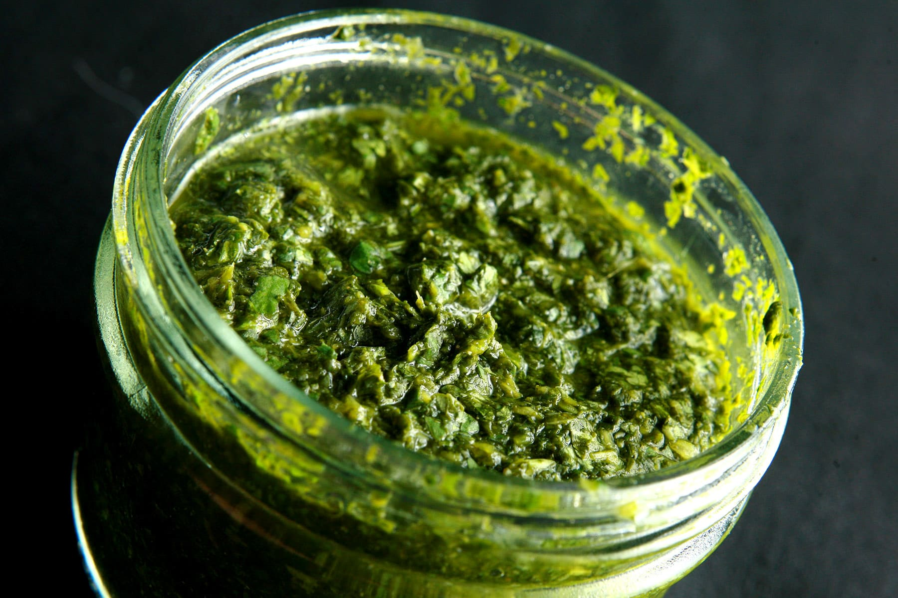 A close up view of a jar of cilantro mint chutney, a deep green dip that looks like pesto.