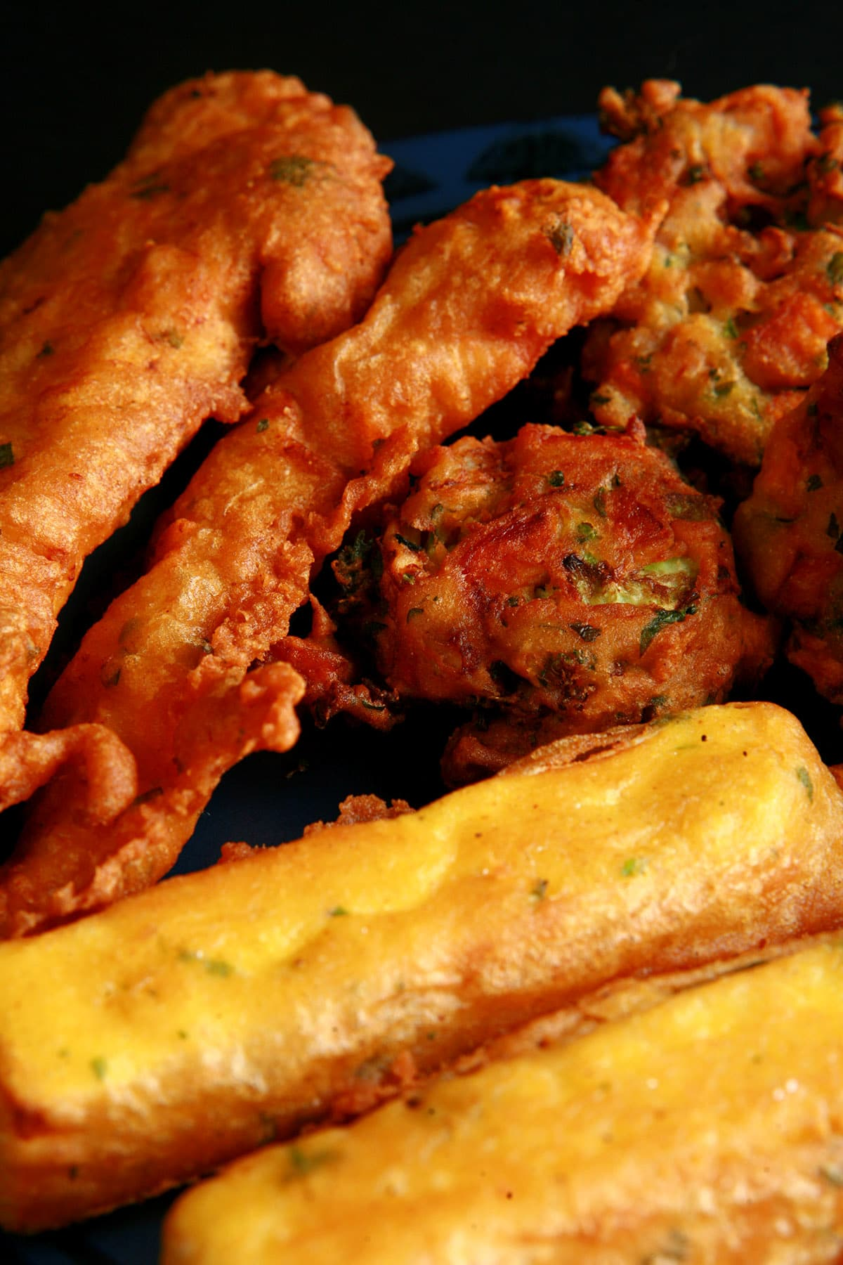 A close up view of a plate of several types of pakora - chicken, paneer and mixed vegetable pakoras.