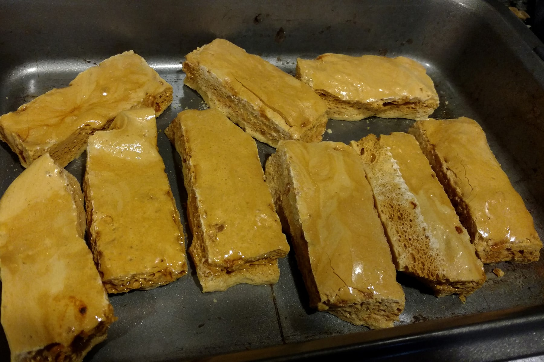 Several long, narrow bars of sponge toffee, arranged in a pan.
