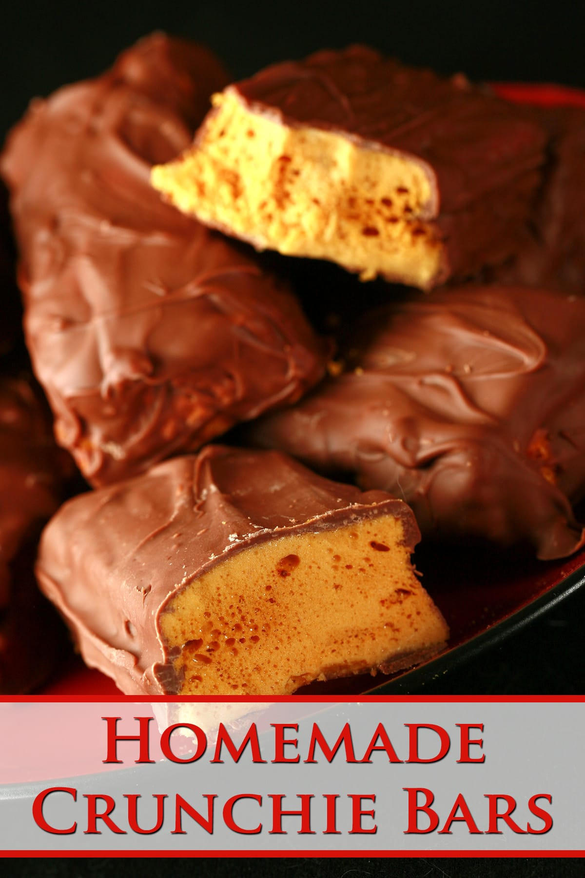 A small red plate is piled high with homemade crunchie bars. One is broken in half to reveal the honeycomb toffee inside.