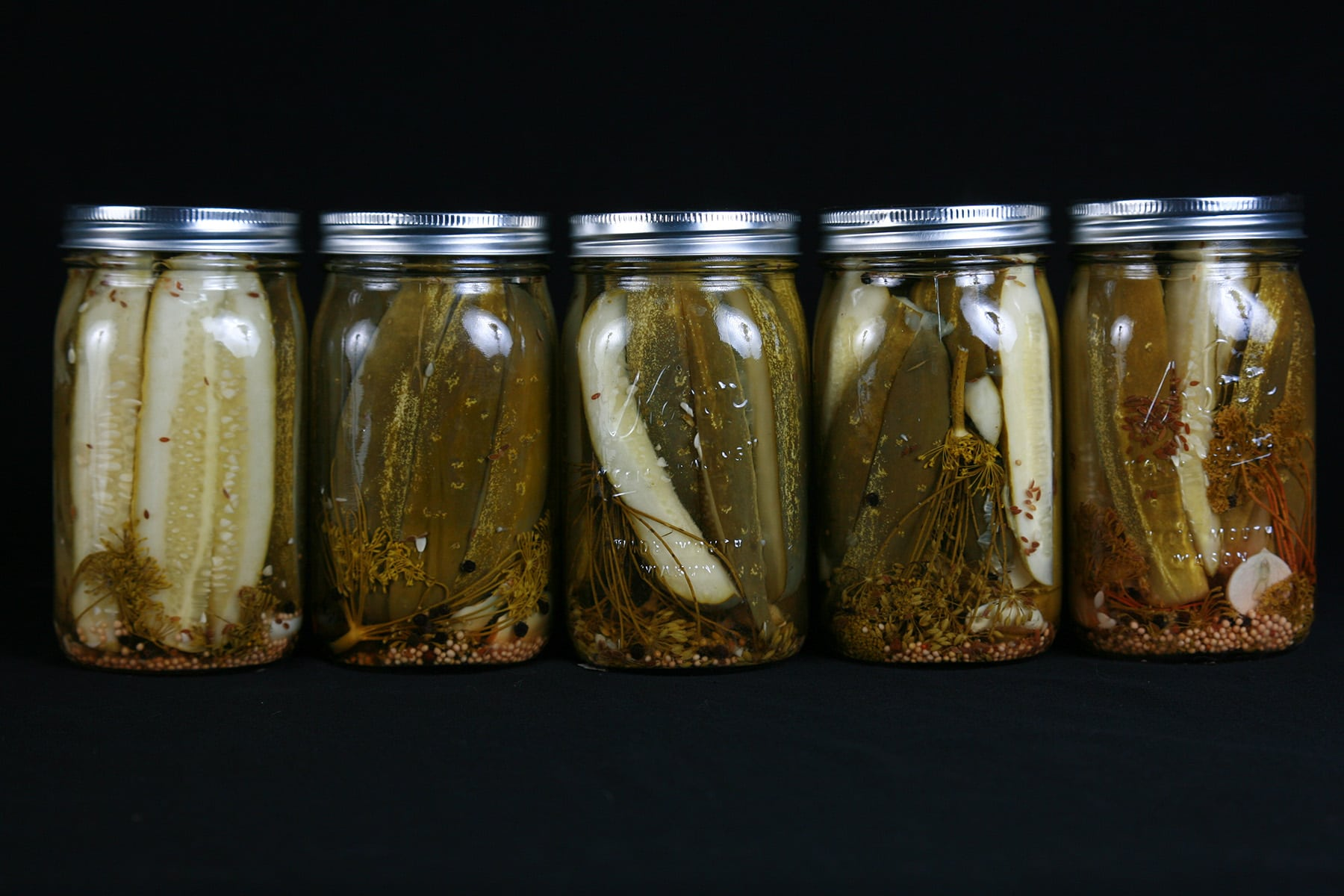 A line of 5 large jars of homemade dill pickles.