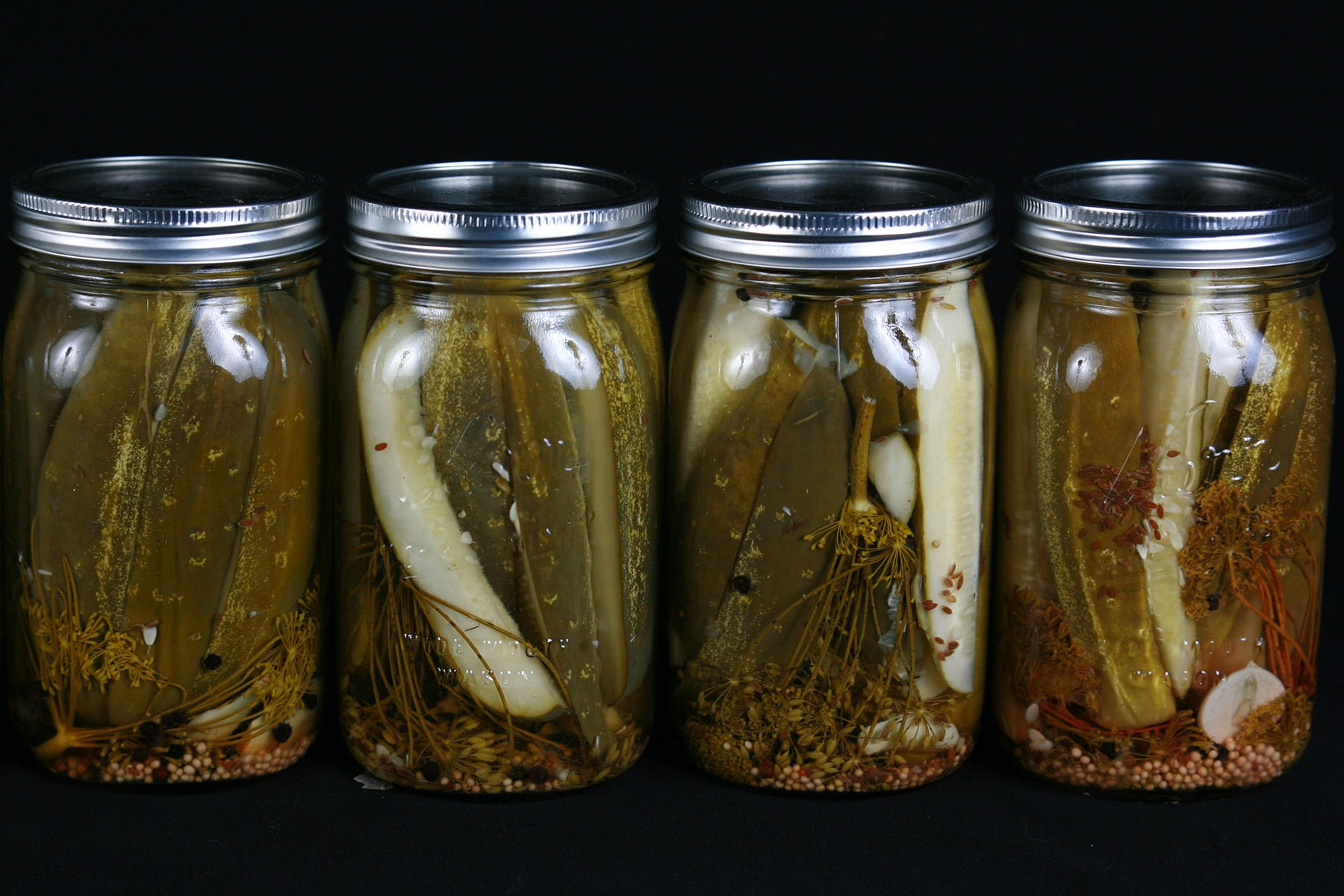 A line of 4 large jars of homemade dill pickles.