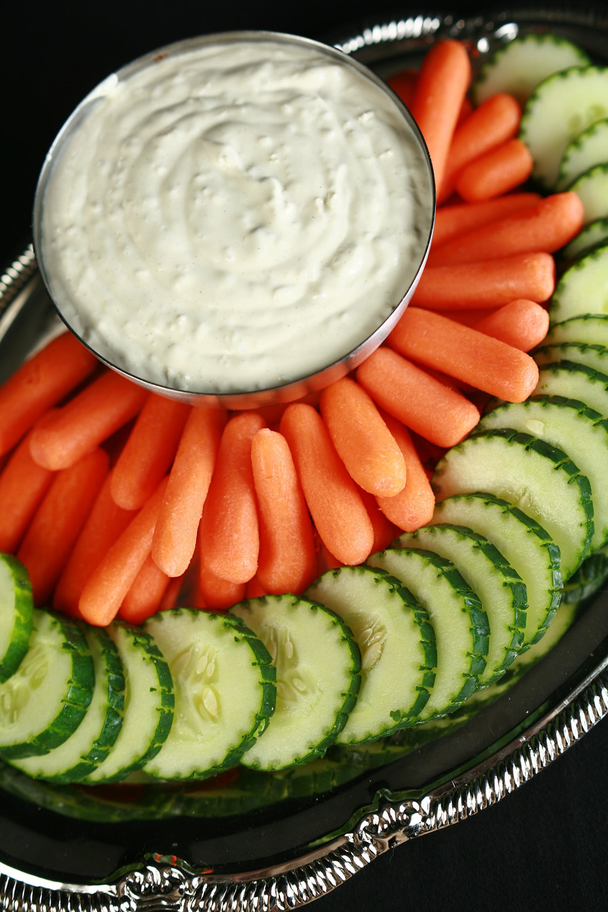 A bowl of ginger wasabi dip, surrounded by cucumber slices and baby carrots.