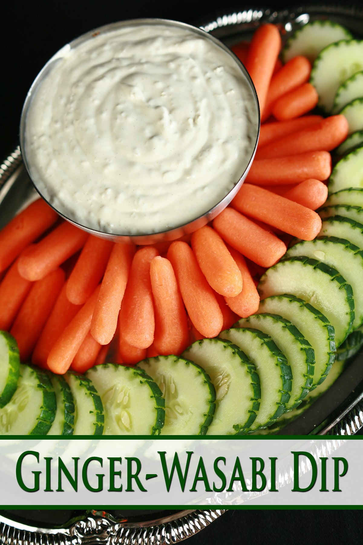 A bowl of wasabi ginger dip, surrounded by cucumber slices and baby carrots.