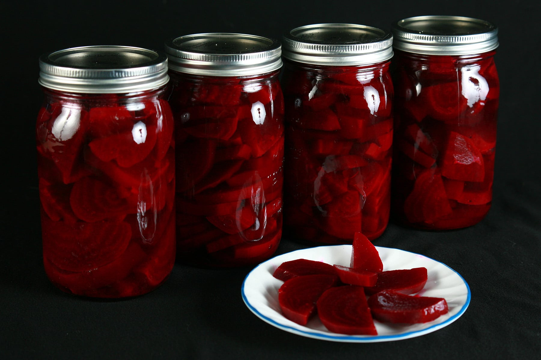 A row of beet pickle jars, behind a plate with pickled beets on it.