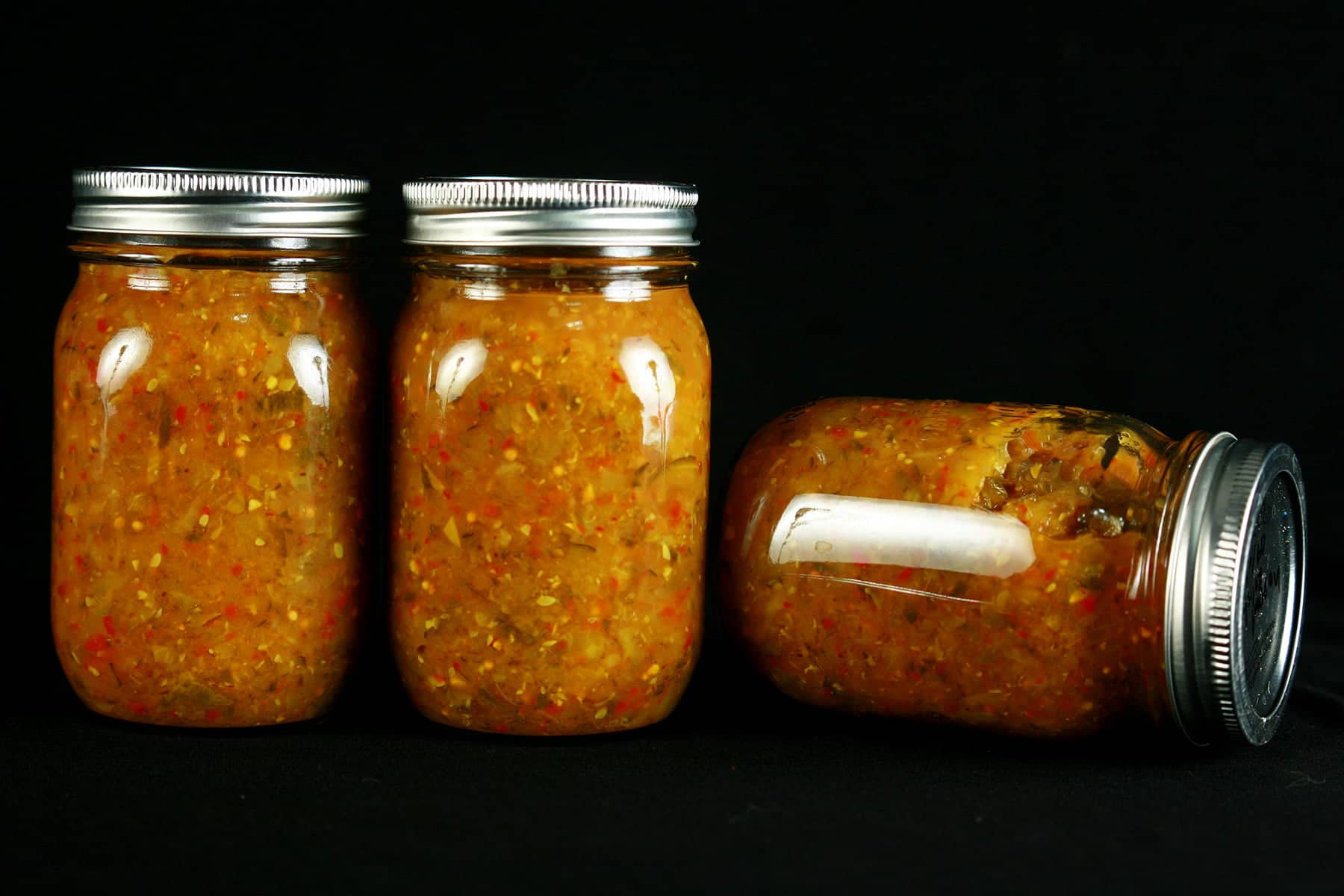 3 jars of Hoppy Dill Pickle Relish. It's a golden orange relish with flecks of dark green and red throughout.