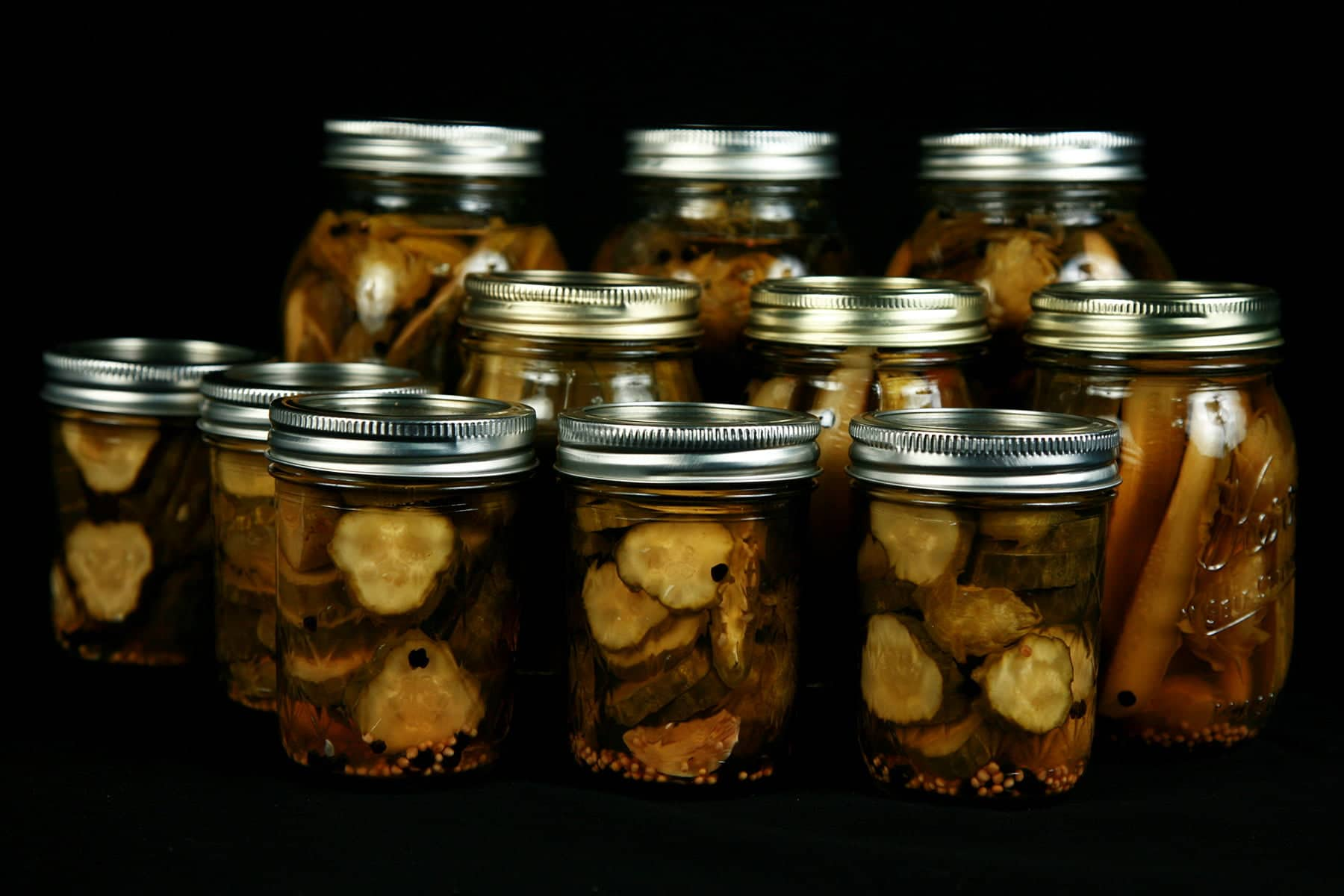 11 jars of hoppy IPA pickles in multiple rows, Hop flowers are visible in the jars, which are against a black background.