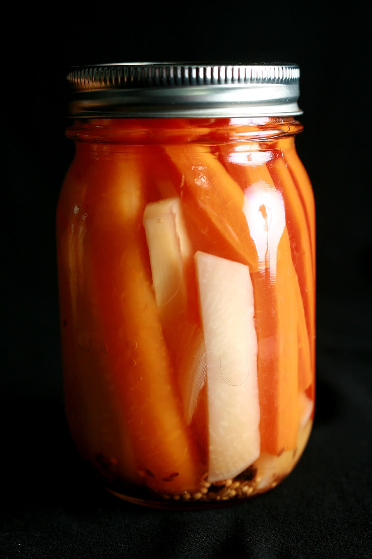 A jar of mixed root vegetable pickles. Spears of carrot, parsnip, and turnip are visible.