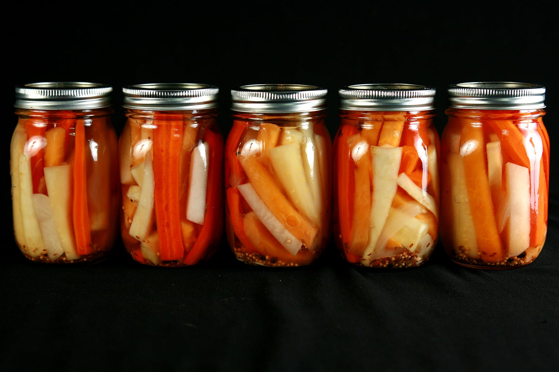 5 jars of mixed root vegetable pickles. Spears of carrot, parsnip, and turnip are visible.