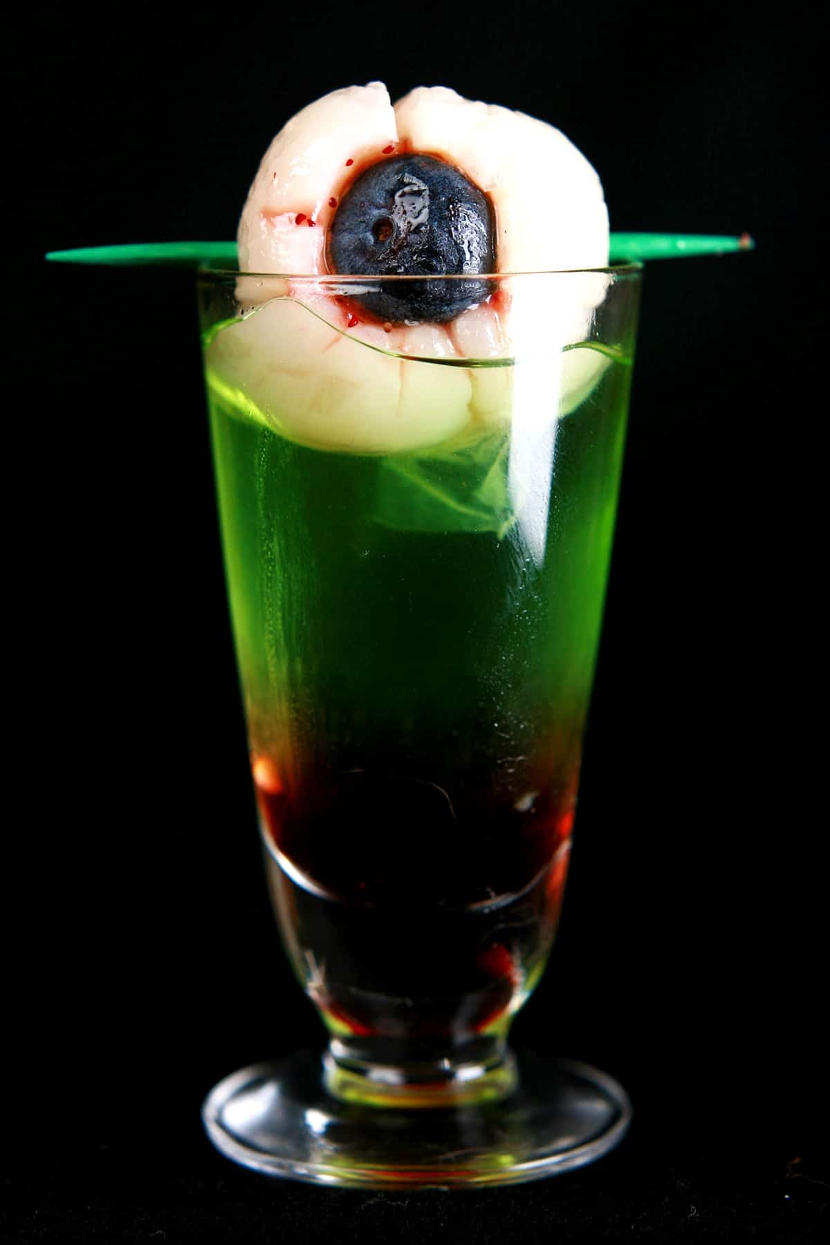 The Bloody eyeball Halloween shot. A bright green Halloween shooter, with red on the bottom. A lychee - filled with red jam and a blueberry - garnishes the top of the shot.