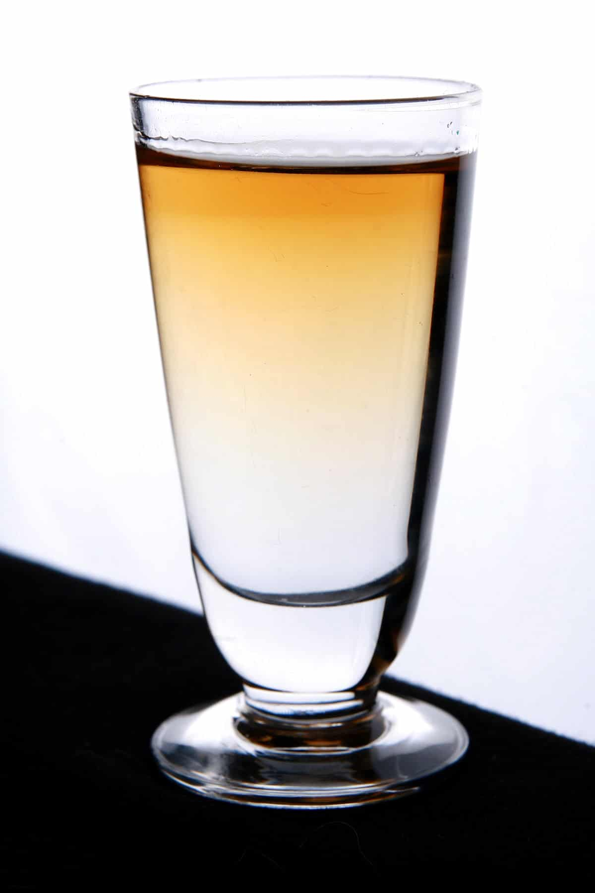 "The ""Halloween Candy"" Shot recipe. A shot glass is shown with clear liquid on the bottom. The top orange layer is seeping into the clear, creating a pretty gradient effect."